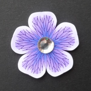 purple polymer clay flower brooch with acrylic cabochon