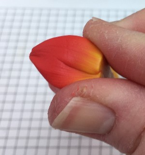 Pinching the polymer clay petal cane into a rounded shape